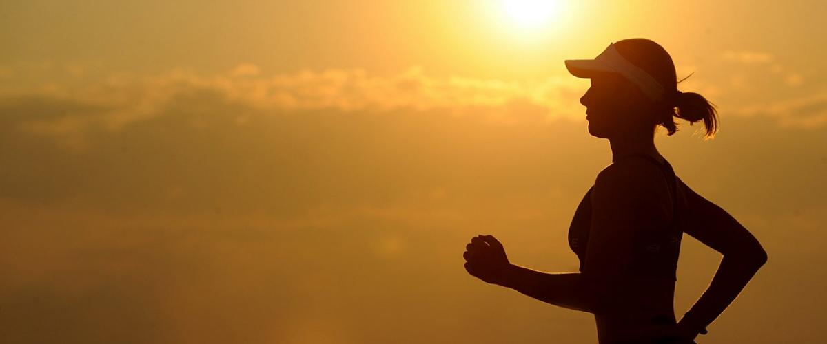 Woman running with the sun in the background
