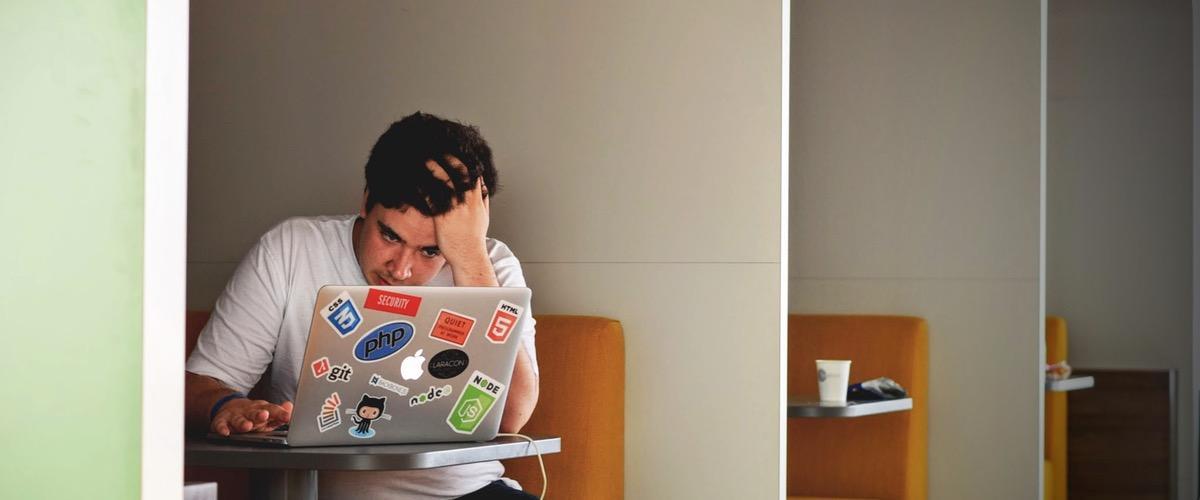 Man in white shirt using a laptop