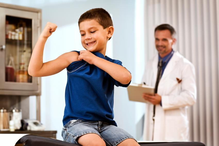 Image of boy flexing arm at doctors appointment