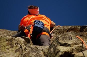Man dressed in orange rock climbing