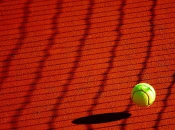 Tennis ball about to land on a clay tennis court